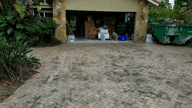 Pressure washing a Boca Raton driveway, & then restoring the faded pavers to a like new condition by National Sealing Company